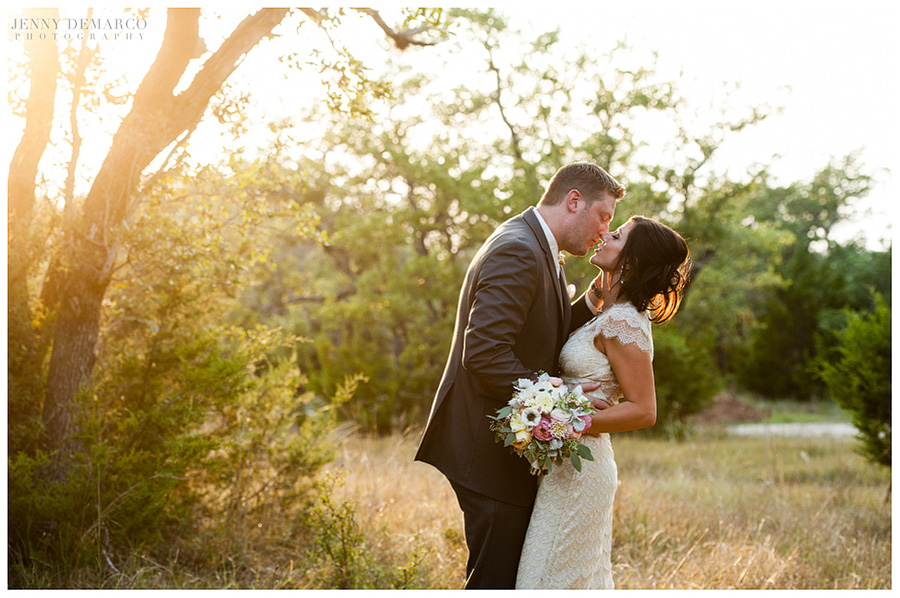 The married couple share a kiss along the beautiful tree line against the Texas Hill Country sunset.