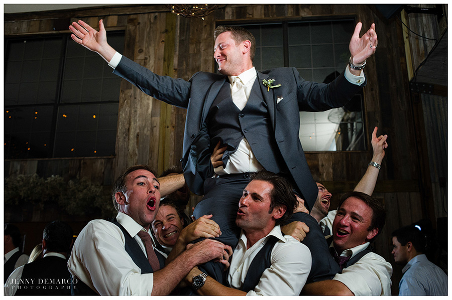 The best men lift the groom up during the reception and celebration.