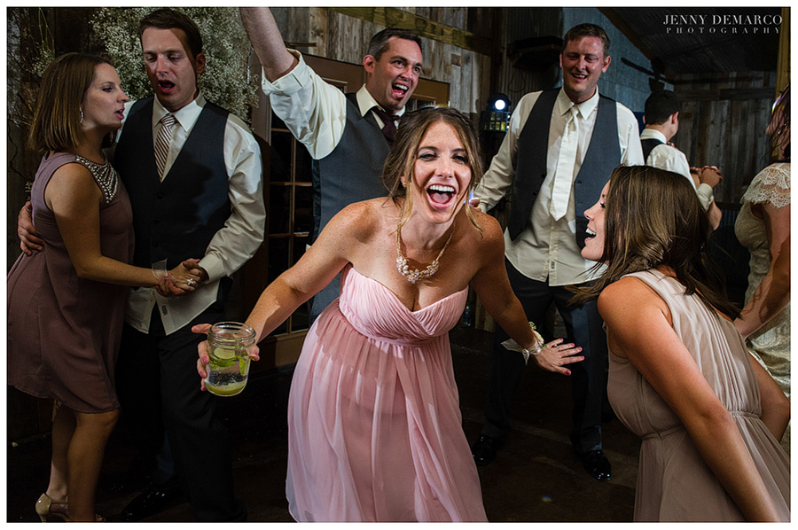 Wedding guests dance and sing along, wearing chic sweetheart gowns.