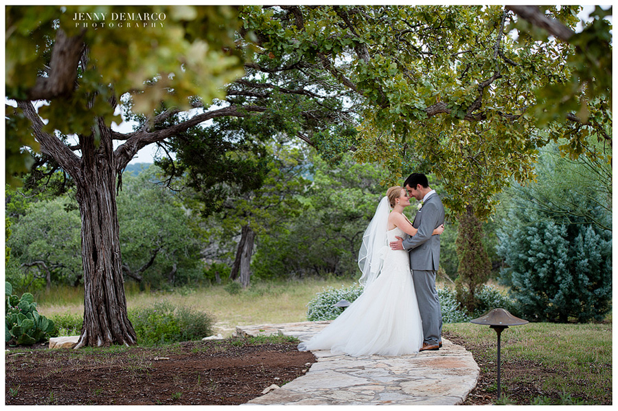 The bride and groom embracing under the beautiful trees at Camp Lucy.