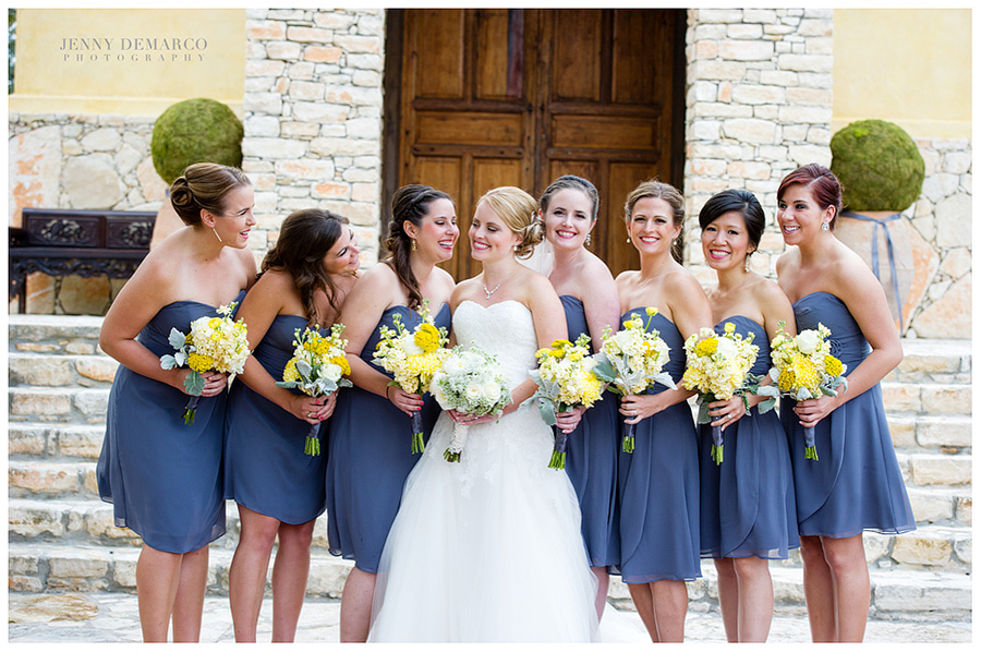 The bridesmaids are all smiles, while surrounding the bride.