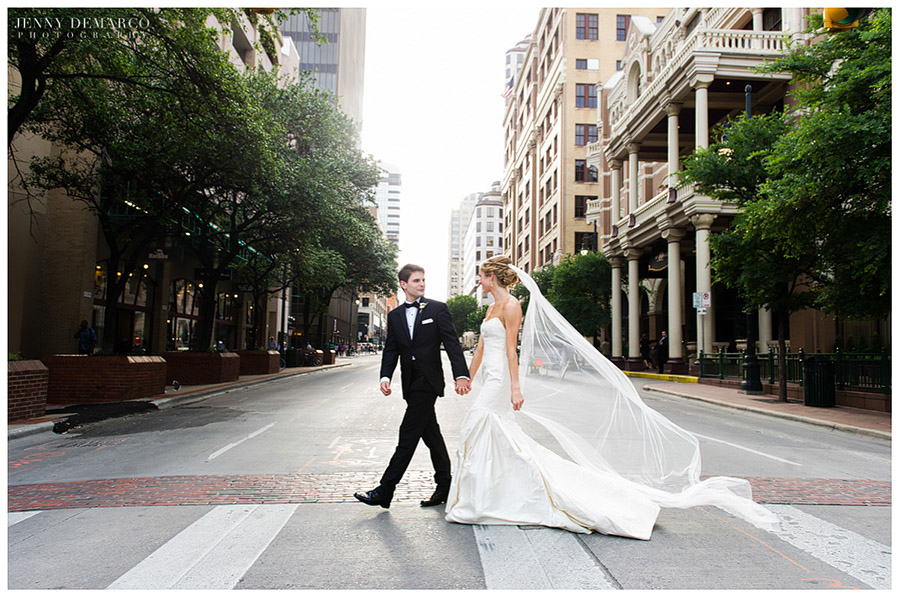 The fashionable couple walk across Sixth Street in downtown Austin.
