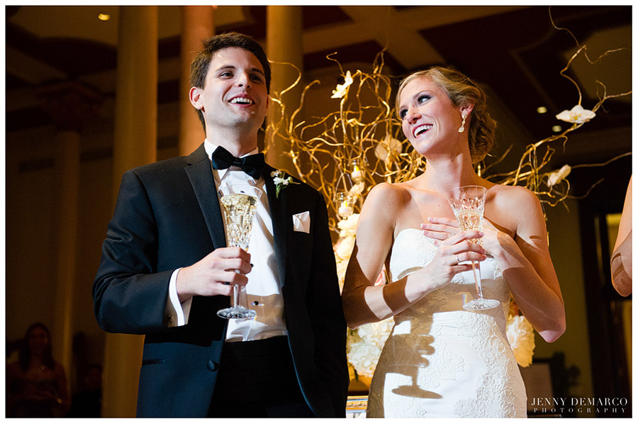 The bride and groom laugh at a speech during the wedding reception photographed by one of Austin's top wedding photographers.