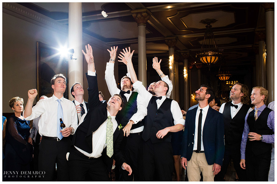 Groomsmen try to catch the lacy garter during the garter toss.