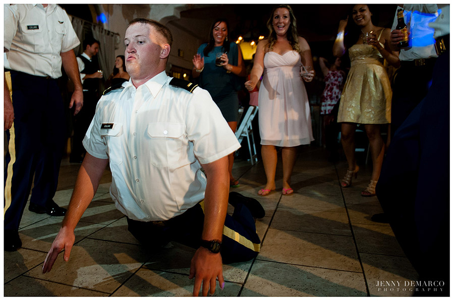A groomsmen does the worm at the wedding reception.