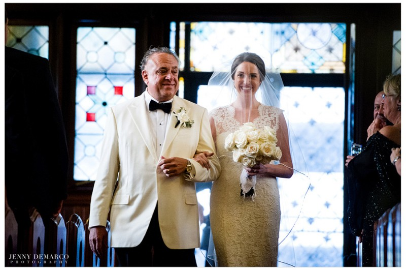 The bride is escorted down the aisle by her father while wearing a cathedral-length veil with blusher.