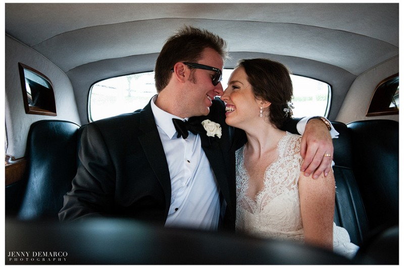 The bride and groom, wearing custom sunglasses, enjoy a private moment in their town car on the way to the Four Seasons Hotel for their formal wedding reception.