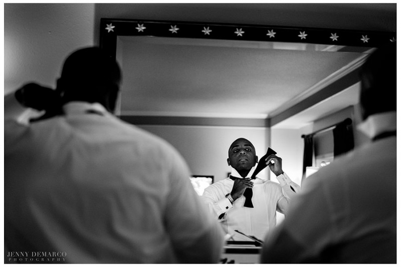 To prepare for the black tie event, the groom hand-ties his satin bow tie in his private suite at the Barton Creek Resort and Spa.