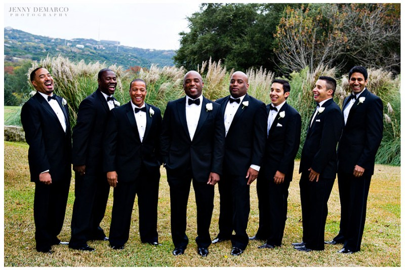 The groom and his wedding party take in the hill country scenery on the resort golf course wearing custom-tailored suits, rose lapels and black satin bow ties.