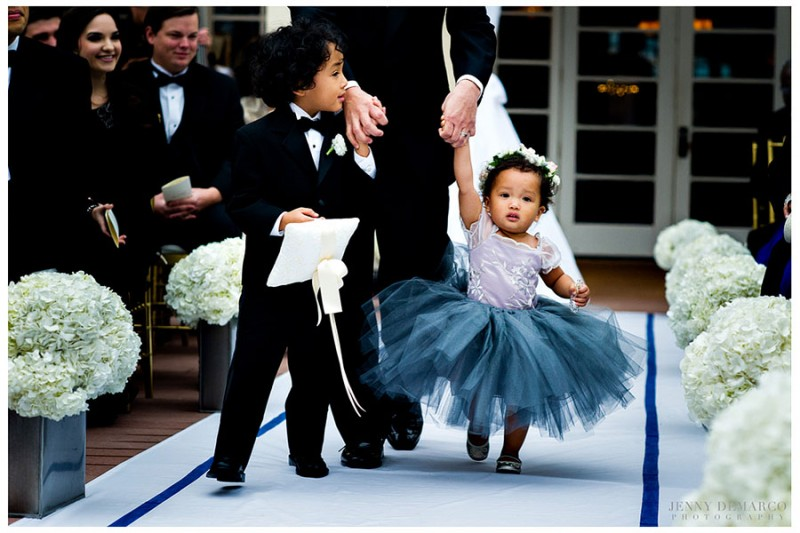 The flower girl and ringer bearer are escorted down the center aisle of the intimate, outdoor ceremony.
