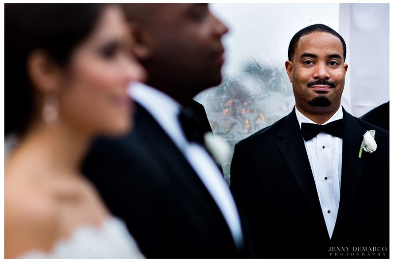 A groomsman, wearing a black dinner jacket, bow tie and white rose lapel, looks on as the bride and groom exhange their vows.