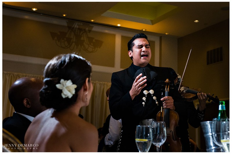 The bride and groom are serenaded by a tradional mariachi performer as is custom in Mexican tradion.