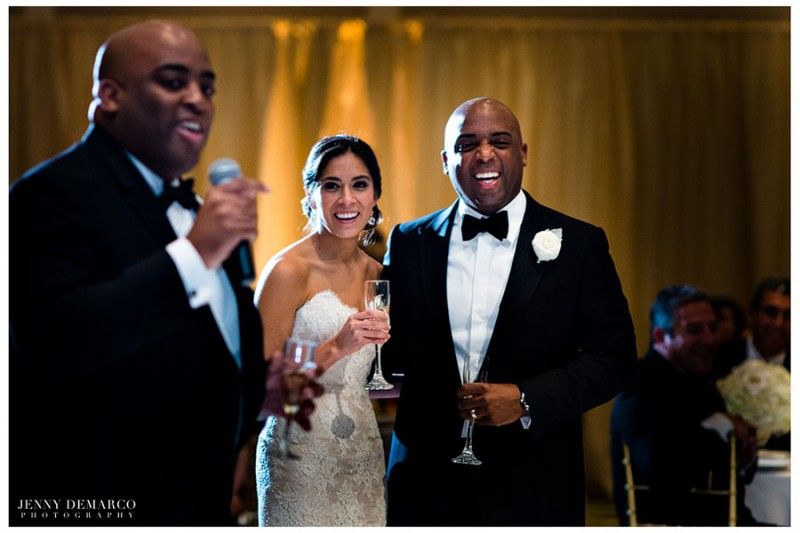 The bride and groom enjoy the toasts offered by friends and family while celebrating with champagne in glass flutes.