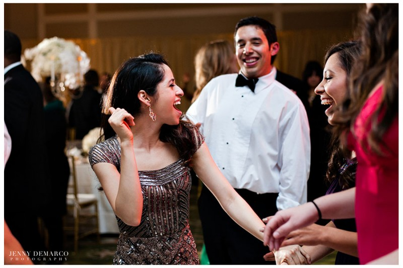 Guests dressed in blacktie formal attire enjoy the dancefloor in the main ballroom at the Barton Creek Resort in Austin, Texas.