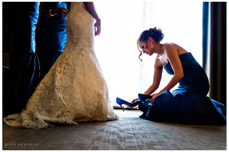 In the Fazio suite at the Barton Creek Resort, a bridesmaid, wearing navy blue satin gown, assists the bride into her Manolo Blahnik Hangisi Jewel Satin Pumps.