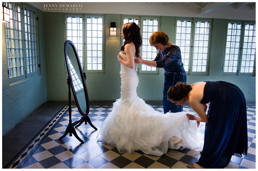 The mother of the bride helps her button her dress in Laguna Gloria's gorgeous turquoise room.