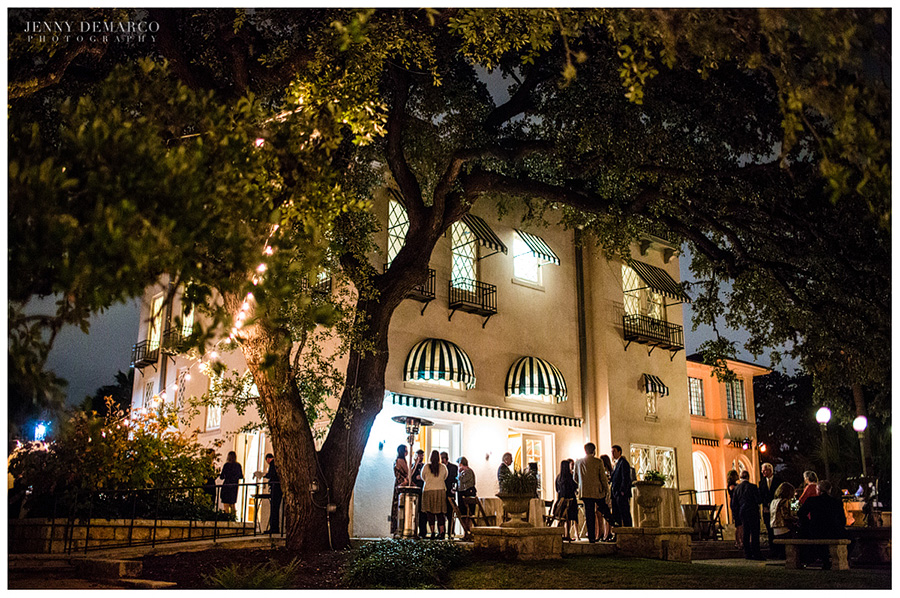 The Contemporary Austin lit up at night, as guest mingle outside.