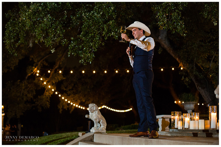 A groomsman gives a true Texan toast, with cowboy hat and drink in hand.