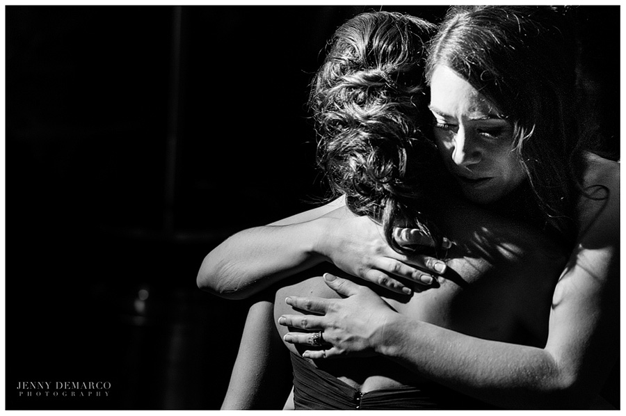 A tender embrace between the bride and her sister.