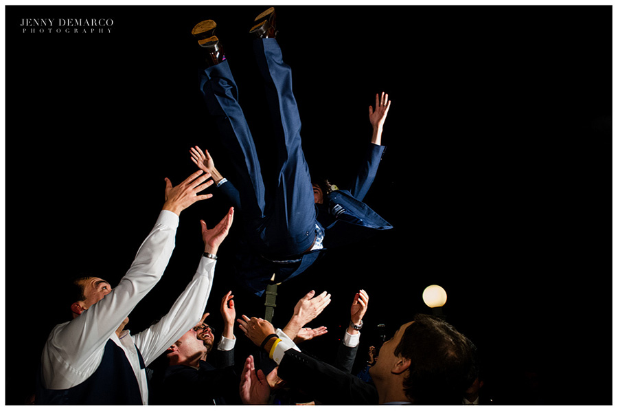The groom getting tossed in the air by his friends.