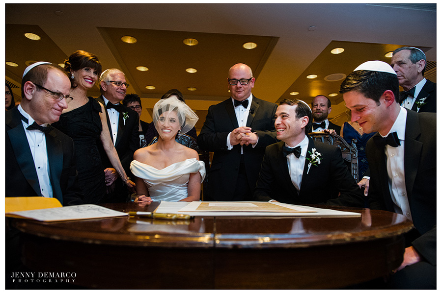 Rachel and Ben signing their customized ketubah infront of their witness.