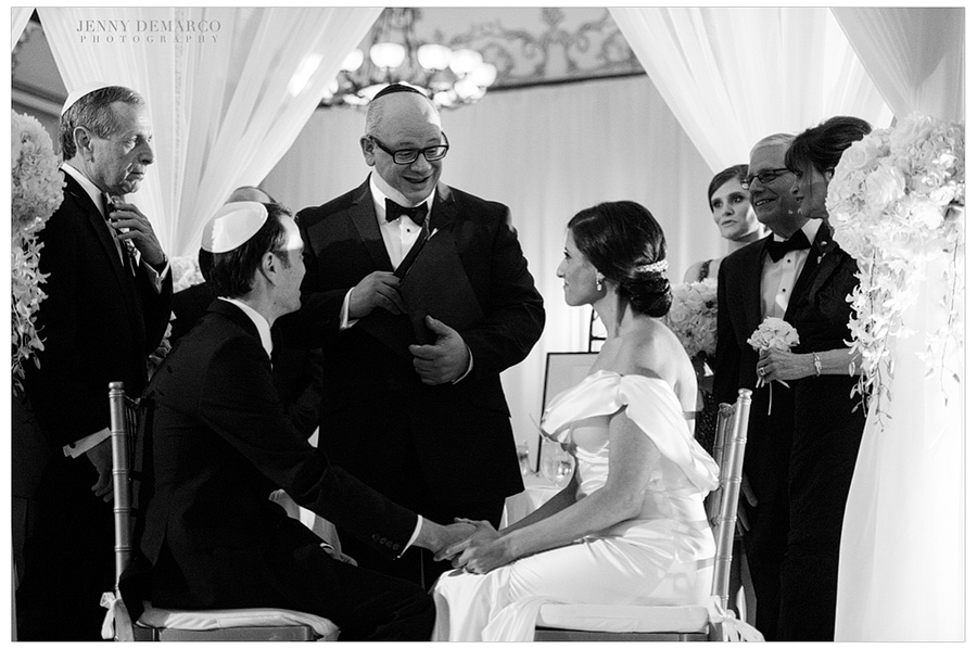 The kiddushin taking place under the huppah at their indoor jewish wedding at the Driskill Hotel in Austin Texas.