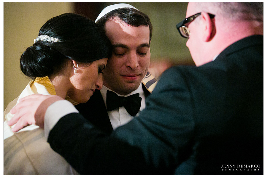Bride and Groom are wrapped a traditional tallit, a jewish prayer shawl.