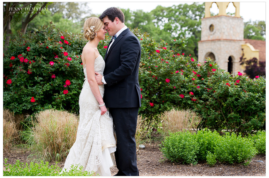 The bride and groom are standing close together in front of a fuchsia colored flower bush.
