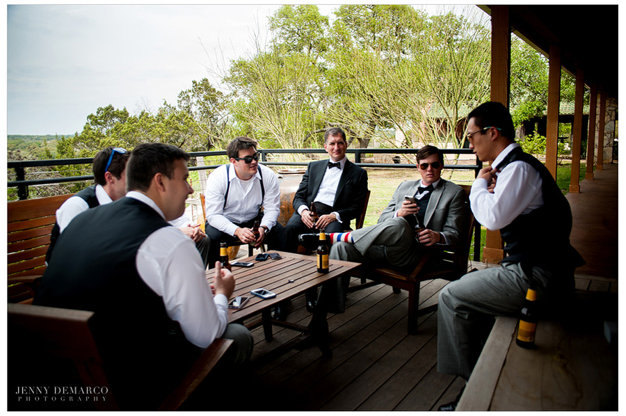 The groomsmen are hanging out with the groom on the deck overlooking Onion Creek in the groom's quarters at Camp Lucy.