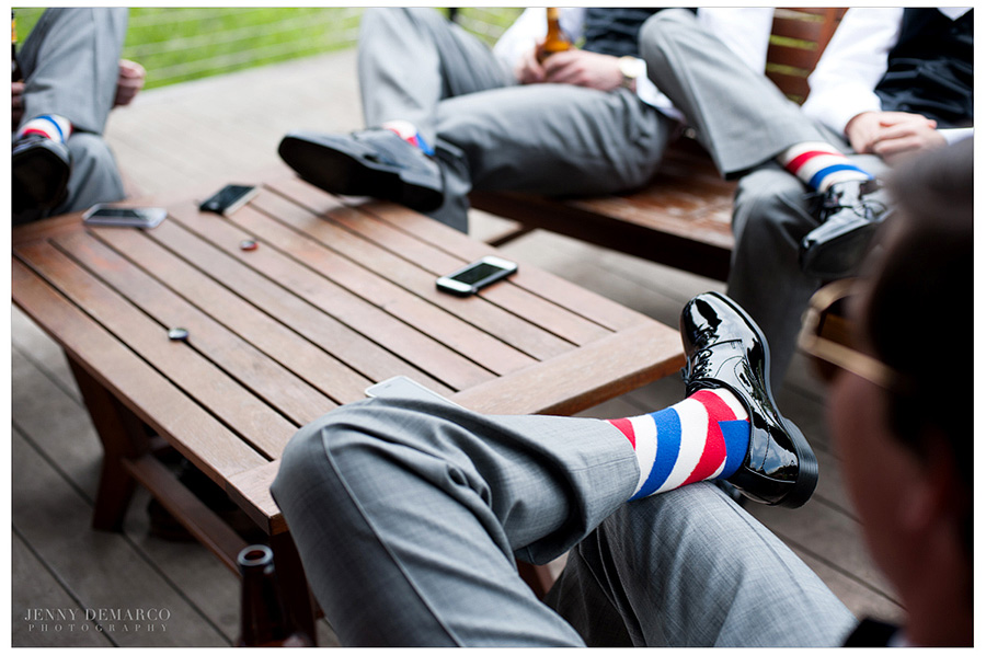 The groomsmen are sitting around a table on the deck showing off their matching red, white and blue socks.