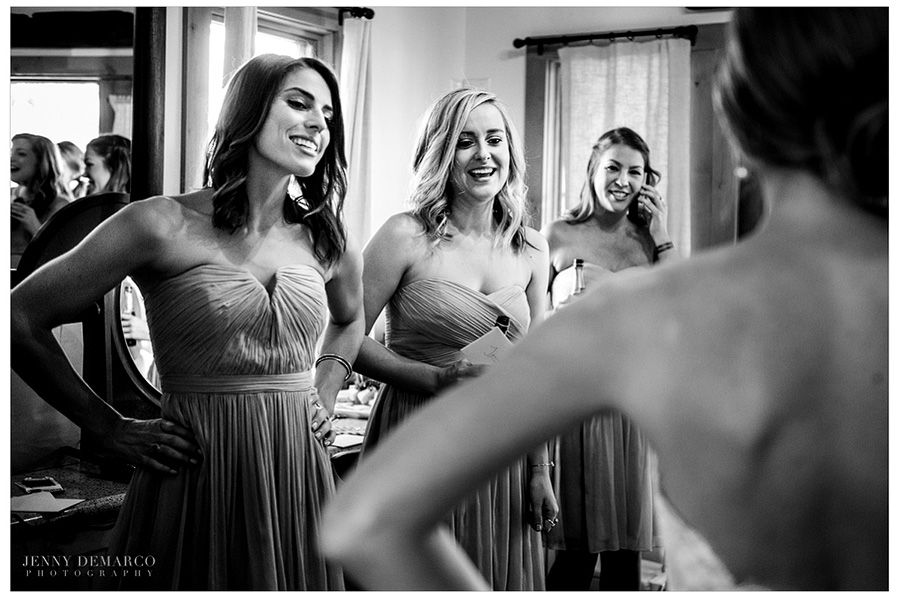 The bridesmaids watching the bride get ready in the bride's cottage.