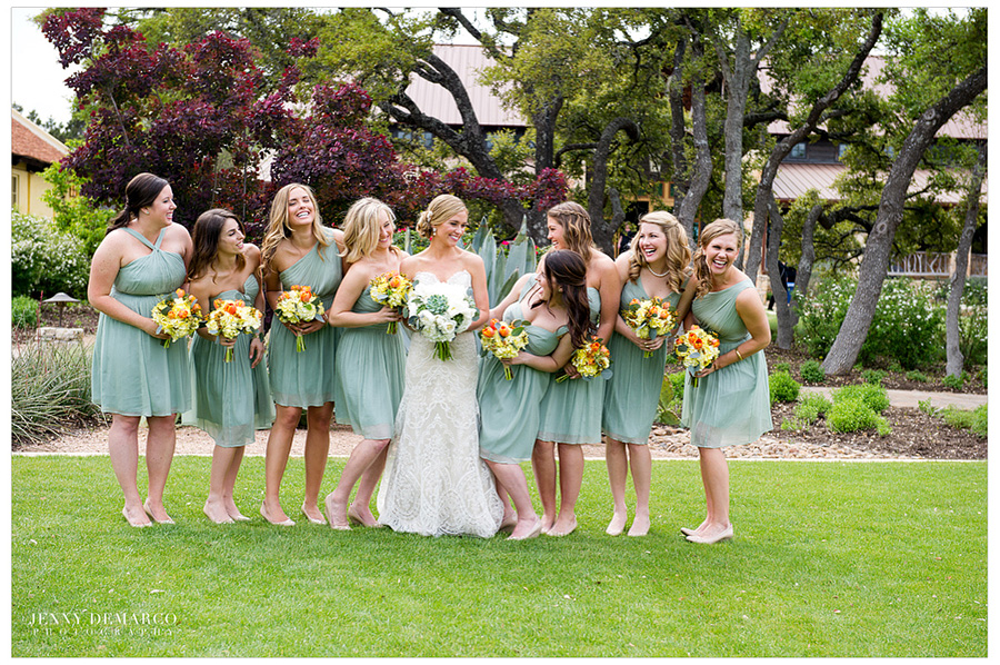The bridesmaids wearing minty green dresses and standing around the bride, holding bouquets, and looking at her.