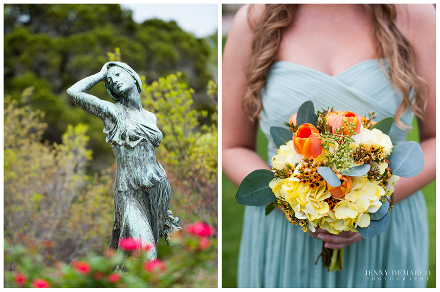 The copper statue of a woman is standing in the middle of a garden with flowers. The photo is a close up image of a bridesmaid wearing a minty green dress and is holding a bouquet with yellow-orange tulips and other citrus-colored flowers.