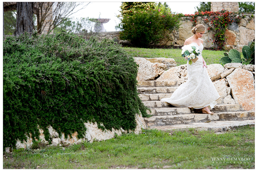The bride is walking down the stone stairs to meet the groom for the first look.