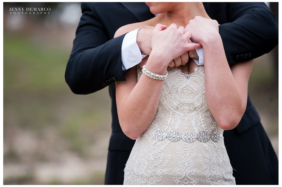 The groom is standing behind the bride and holding her in his arms. The bride is holding his hands.