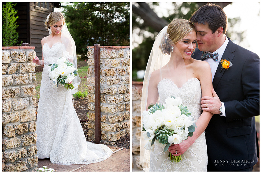 The bride is wearing a lacy off-white wedding dress and is looking down at her bouquet while standing by a rusty iron gate. The groom is standing behind the bride and holding her arm with their heads touching.
