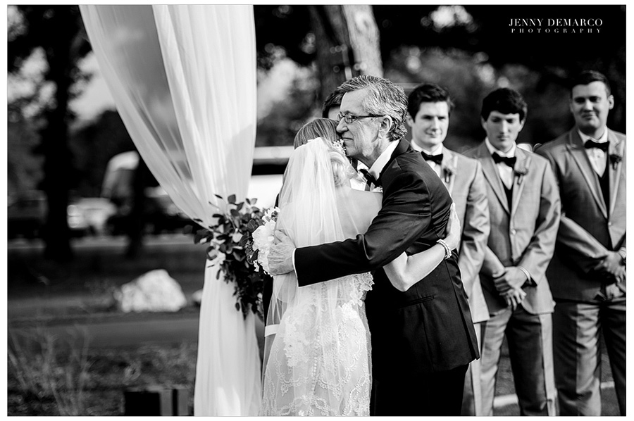 The father giving away the bride and hugging.