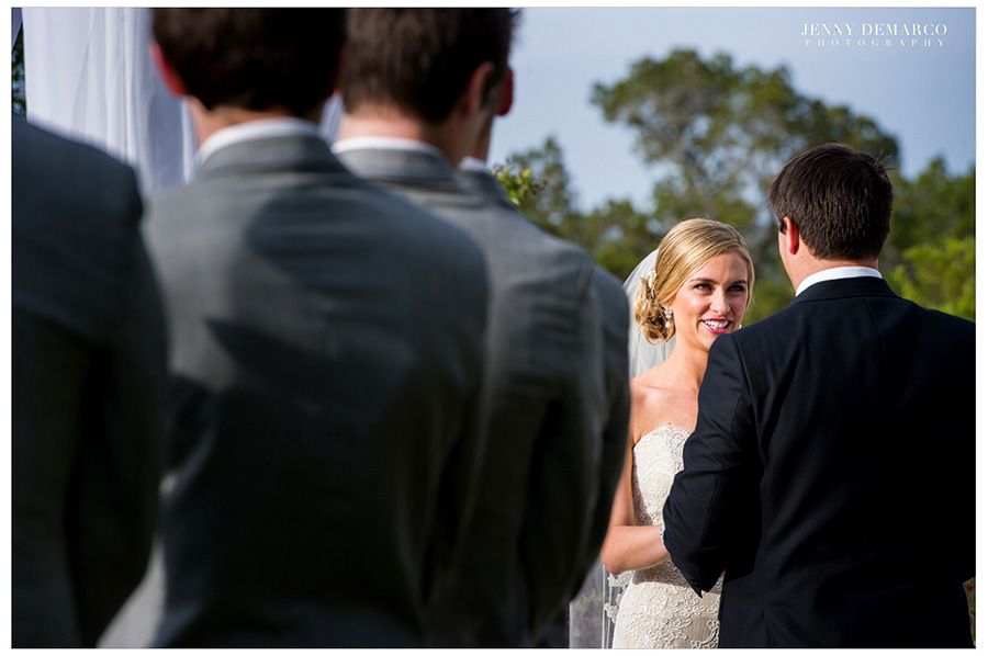 The bride and groom are holding hands and looking into each other's eyes while the groomsmen are looking at them.