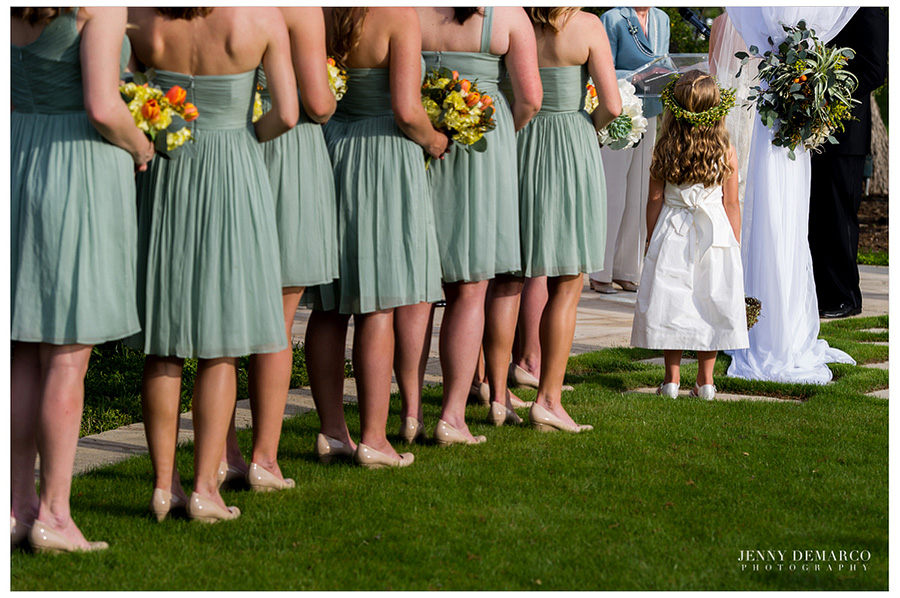 The bridesmaids are lined up wearing minty green dresses and the flower girl is standing in front of them wearing a white dress and a wreath on her head.