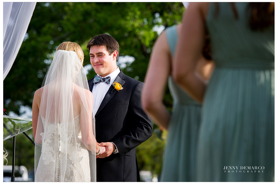 The groom is looking at the bride and is smiling while holding her hands.