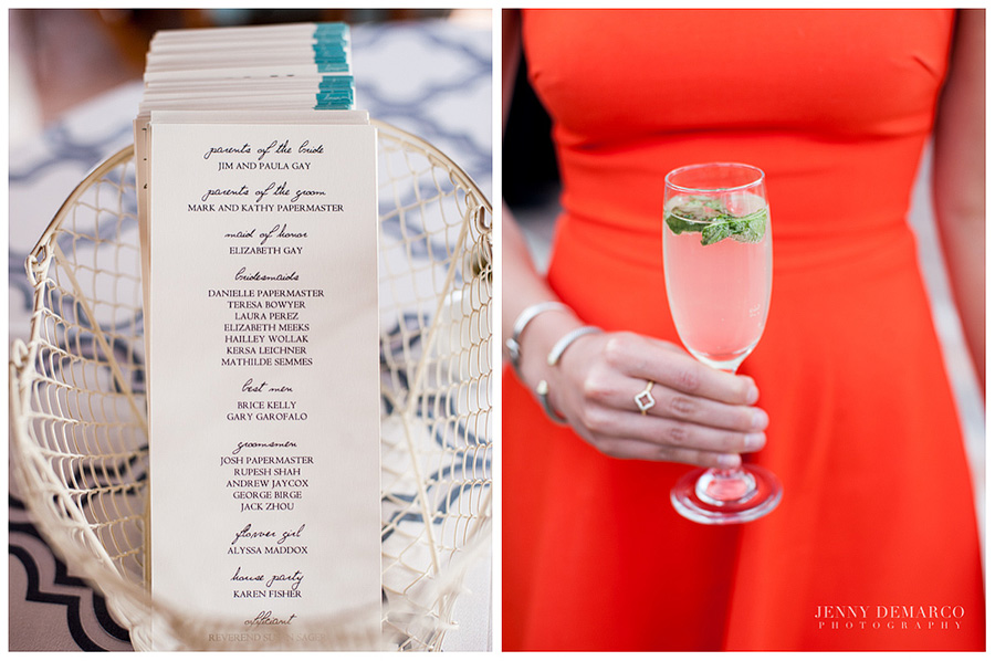 The woman is wearing a red dress and is holding a cocktail drink. The pile of cards has the list of the wedding party on them.