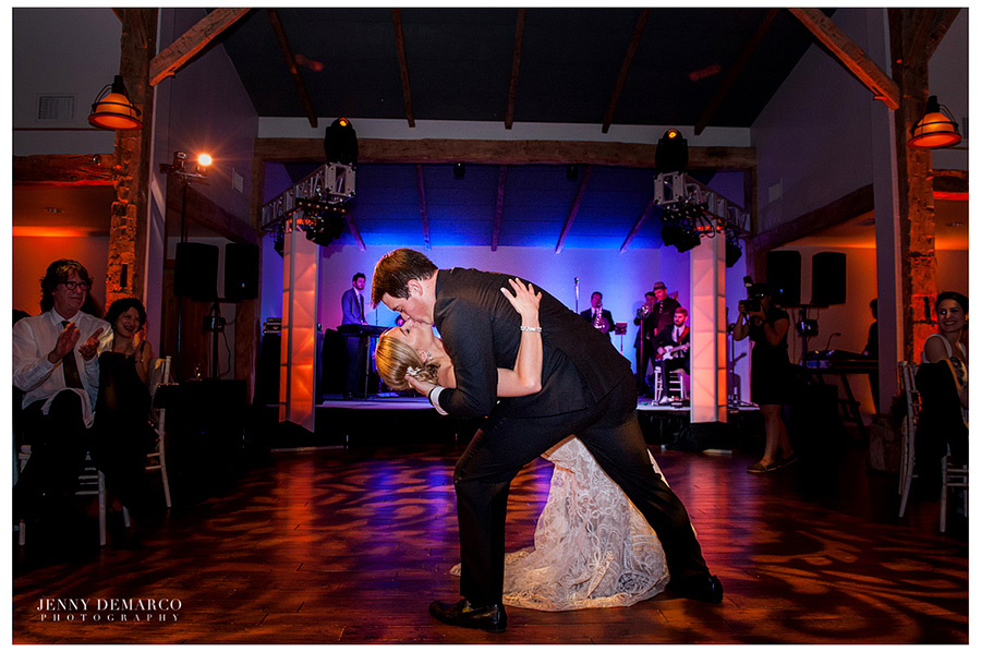 The groom is dipping the bride while giving her a kiss on the dance floor in the Ian's Chapel Events Hall.