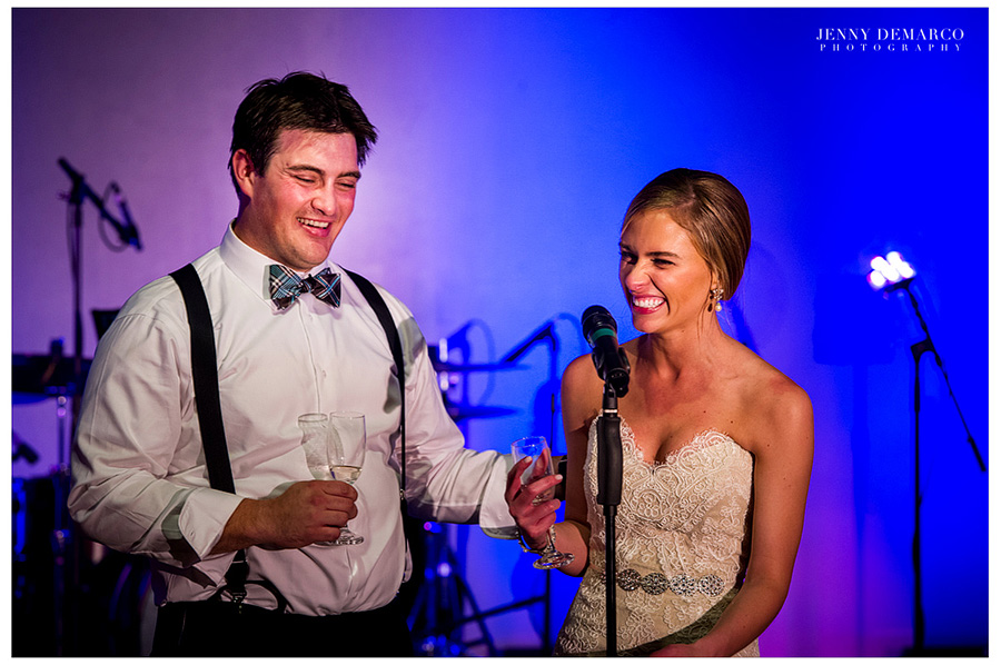 The bride and groom are laughing during the toast at their reception.