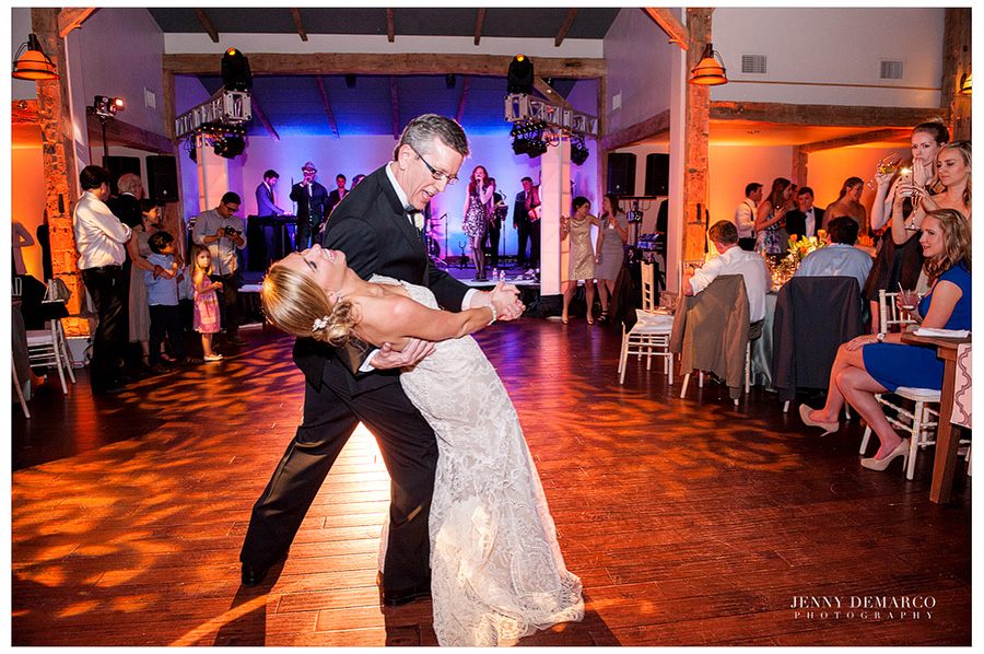 The father of the bride is dipping the bride while doing the traditional father daughter dance in the Ian's Chapel Events Hall.