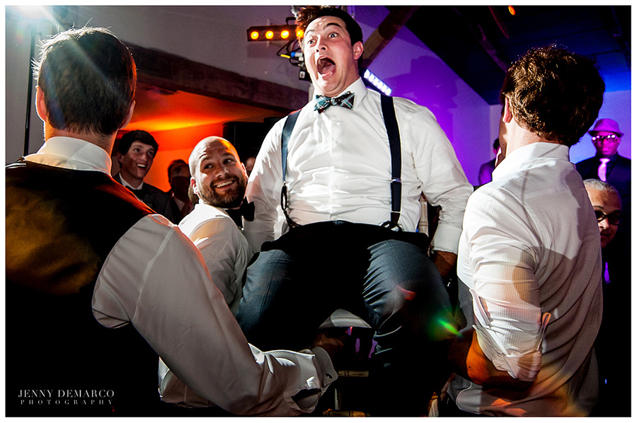 Some men are lifting up the groom is his chair for the jewish traditional Hora, or chair dance.