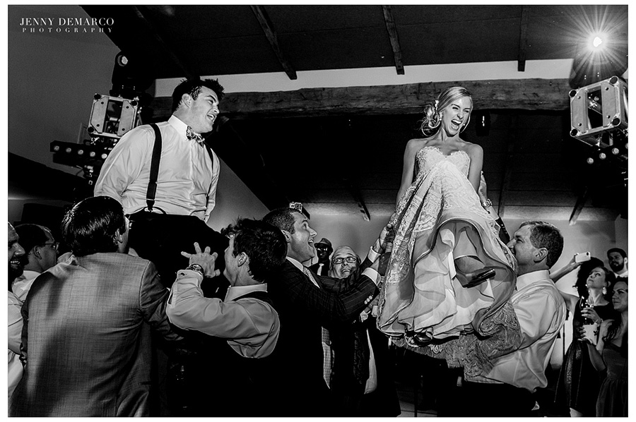 Men are lifting up the bride and groom in chairs for the jewish traditional Hora (chair dance).