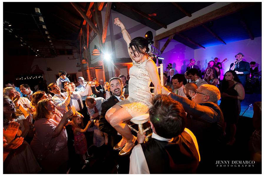 Another woman is being lifted up in a chair for the Hora dance.