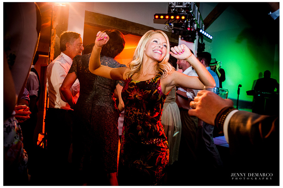 A woman in a black and red dress is dancing at the reception in the Ian's Chapel Events Hall.
