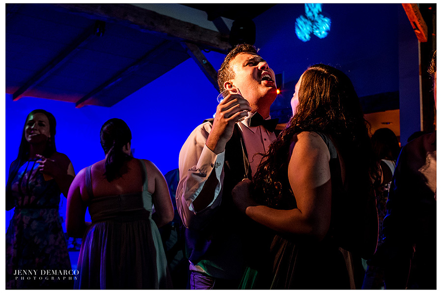 A woman is dancing with a man who is singing along to the song that is playing at the reception in the Ian's Chapel Events Hall.