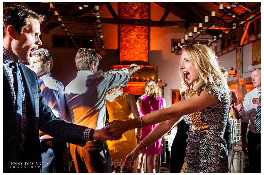 A man and woman dancing together while making dramatic faces at the reception in the Ian's Chapel Events Hall.